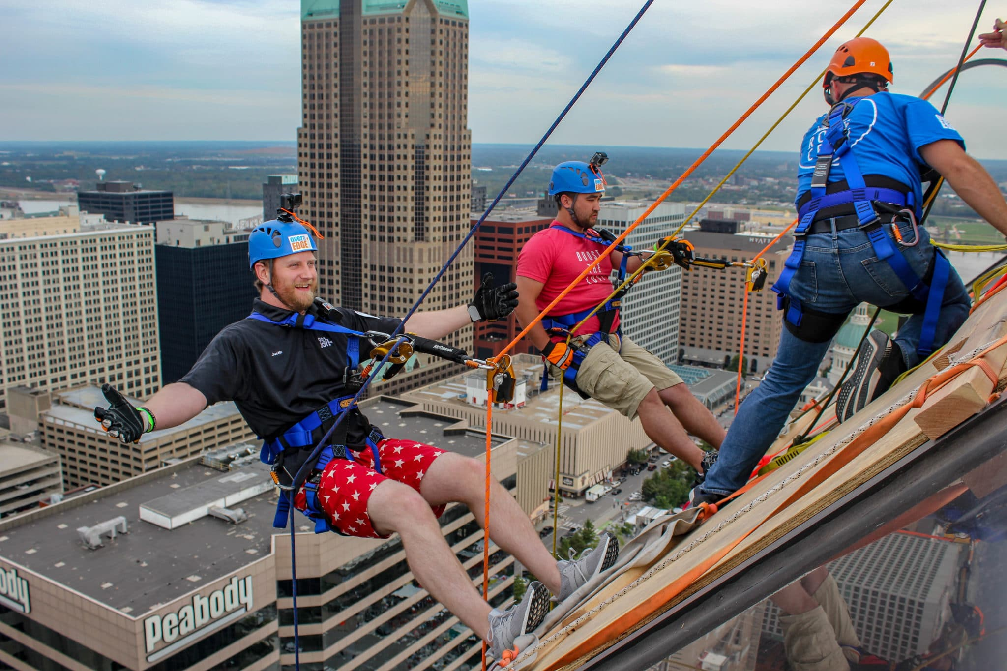 Two people wearing protective gear and ropes lean off the side of a building