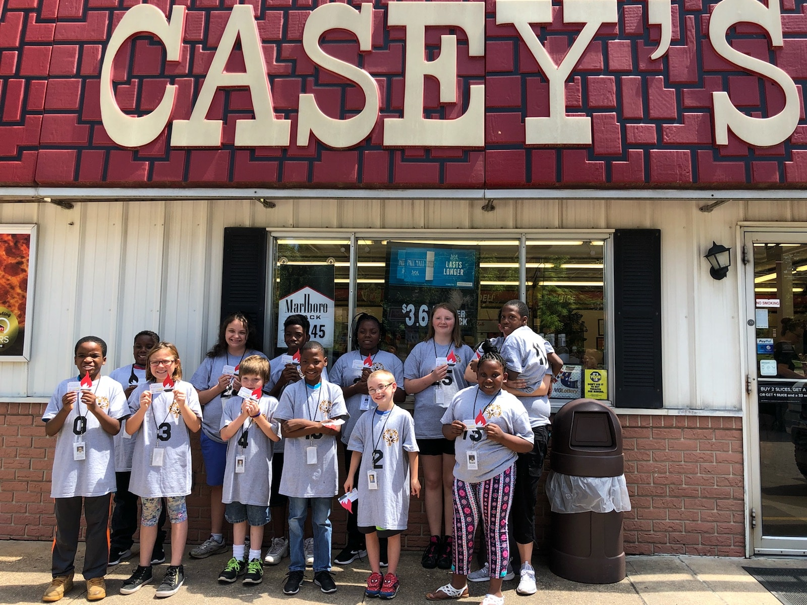 A group of Young Athletes stand outside a Casey's General Store and hold a paper icon