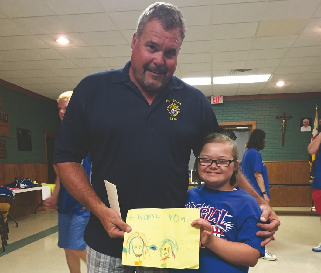 Knights of Columbus member poses with young athlete holding a a piece of paper with a drawing on it
