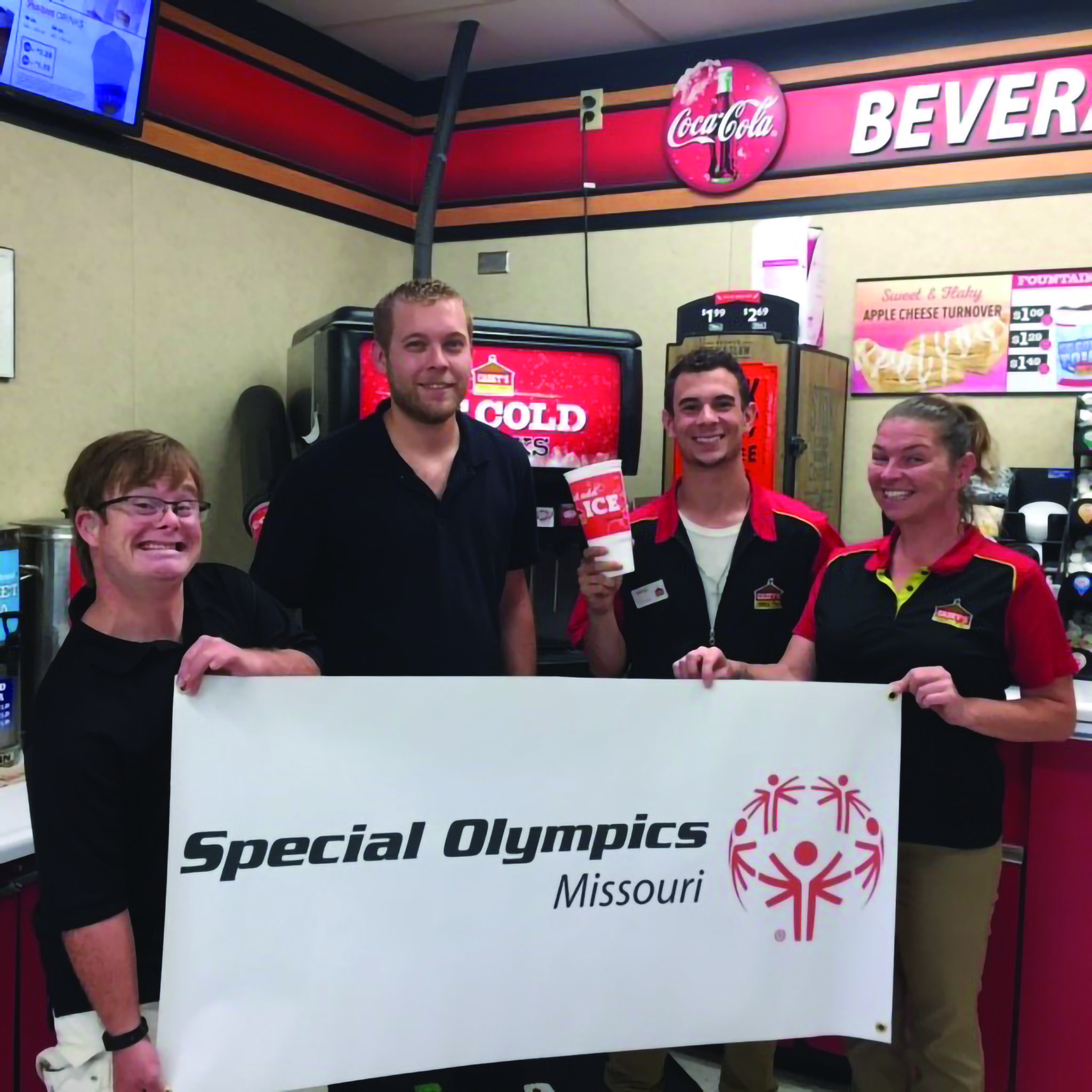 An athlete poses for a photo with Casey's General Store employees while holding a SOMO banner