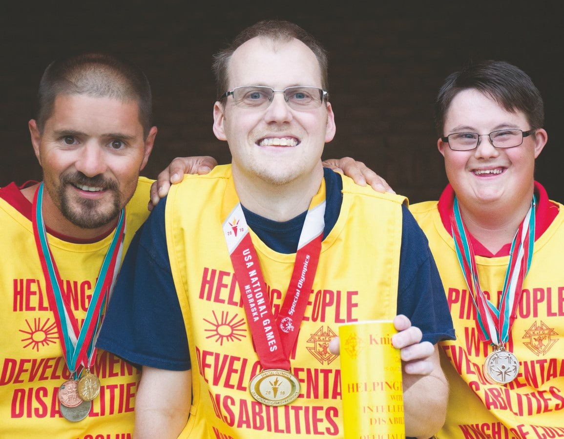 Three athletes with medals around their neck pose, smiling, for a photo while wearing yellow Knights of Columbus fundraising bibs