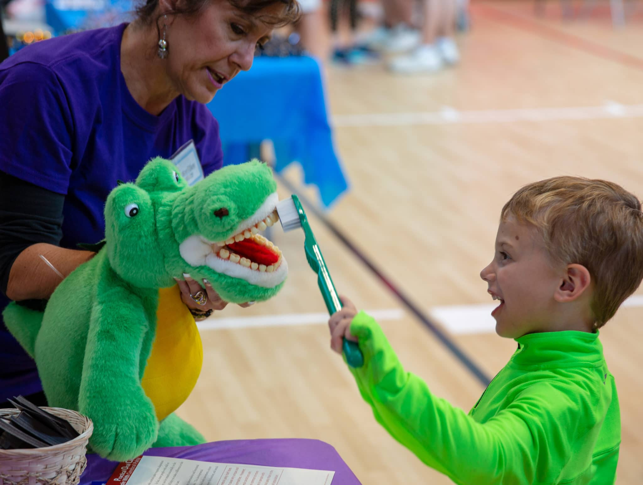 A Young Athletes uses an oversized toothbrush and a stuffed animal to show a volunteer the right way to brush teeth