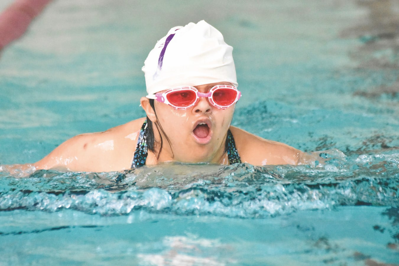 A swimmer with rose-colored goggles comes out of the water to take a large breath