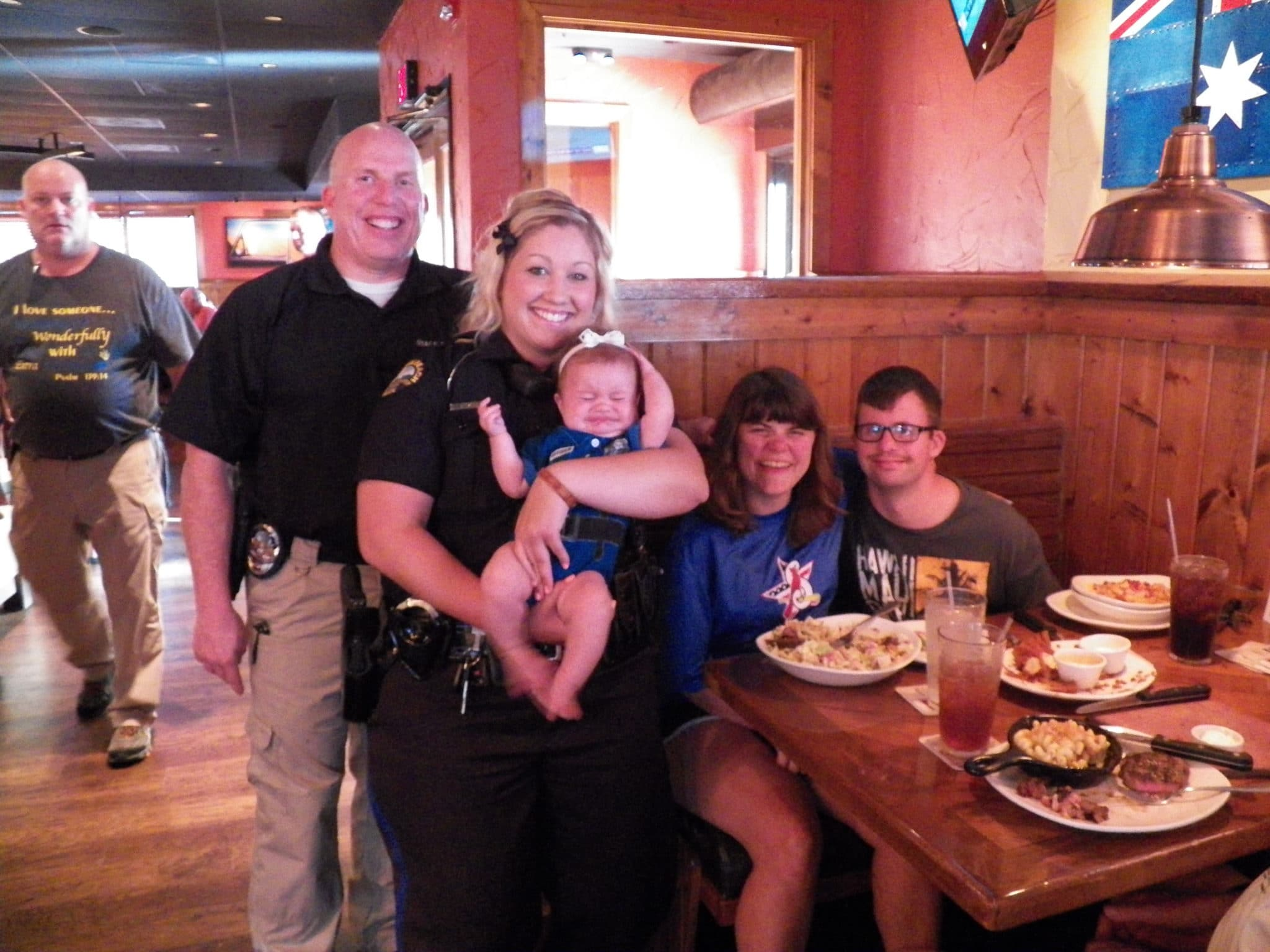 Two law enforcement officers hold a crying baby in a restaurant