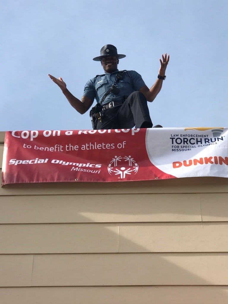 A law enforcement officer poses hands up on top of a Dunkin' Donuts store