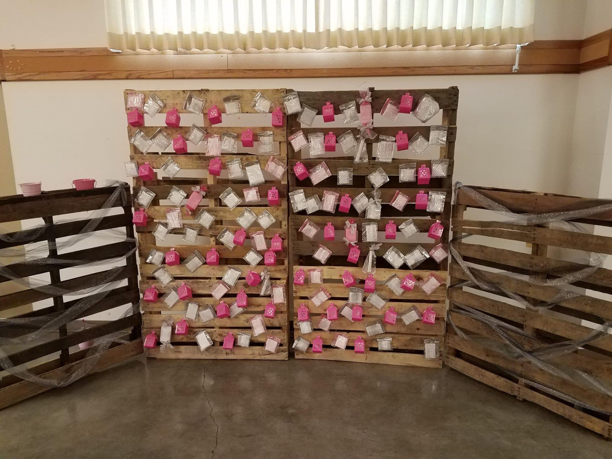 Pink and white envelopes are taped to a couple of pallets