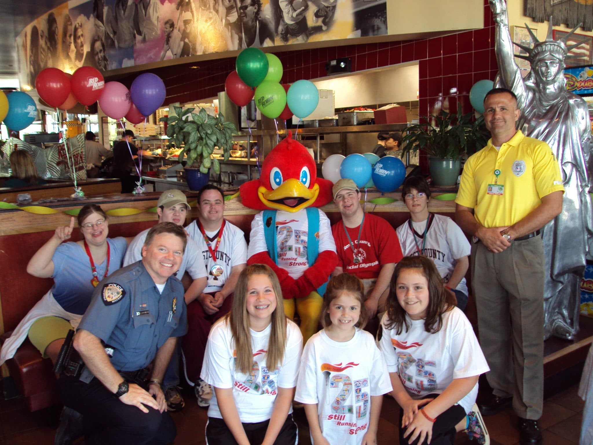 Athletes and law enforcement officers pose for a photo in a restaurant
