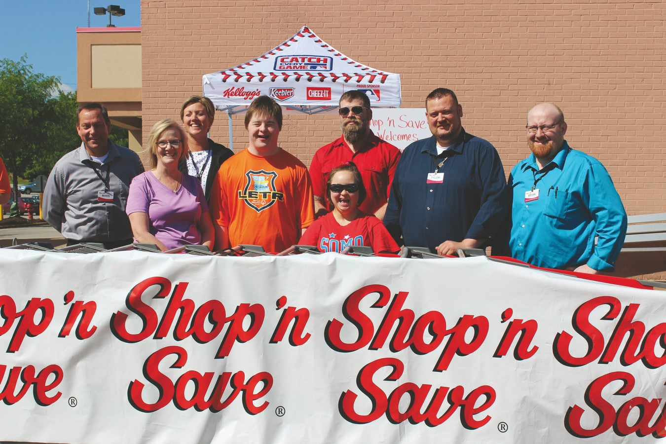 Group smiles and poses behind a Shop'n Save banner