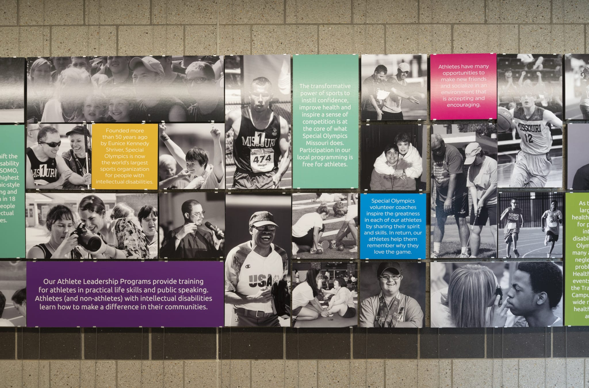 An interior photo of a wall with black and white photos of athletes at the Training for Life Campus