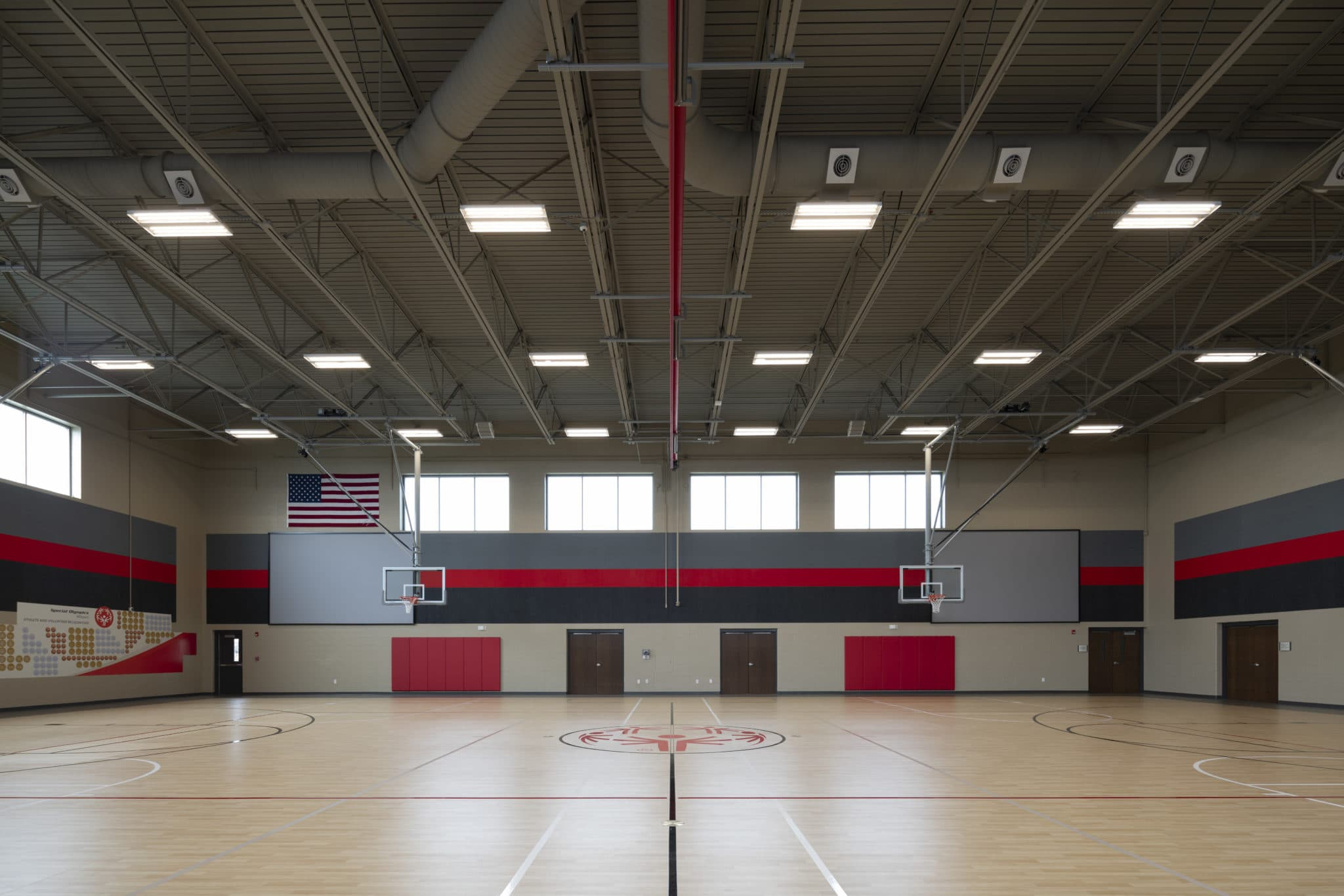 A gymnasium with two basketball hoops, two large screens, and a SOMO logo at center court
