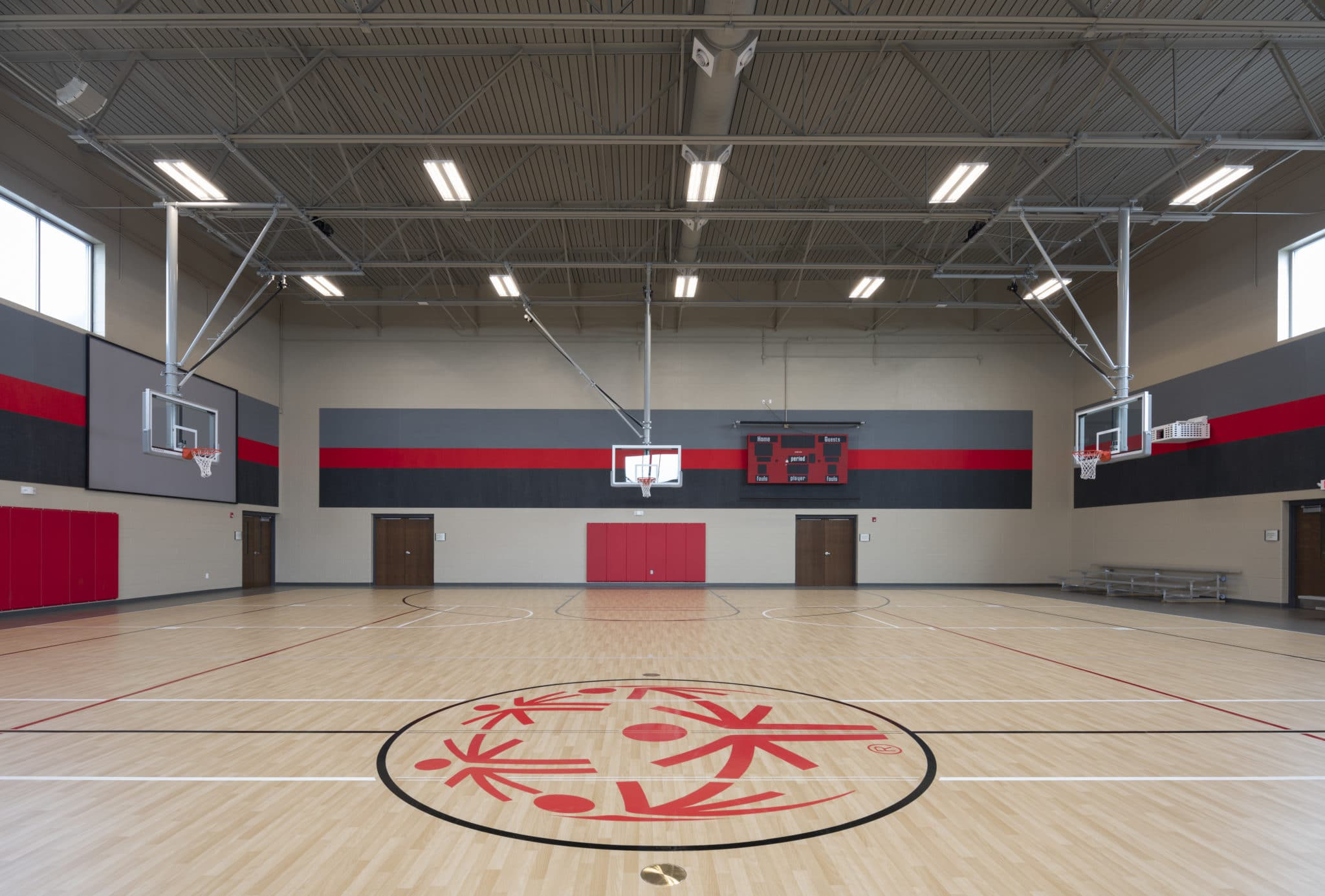 A gymnasium with three basketball hoops, a scoreboard, and a SOMO logo at center court