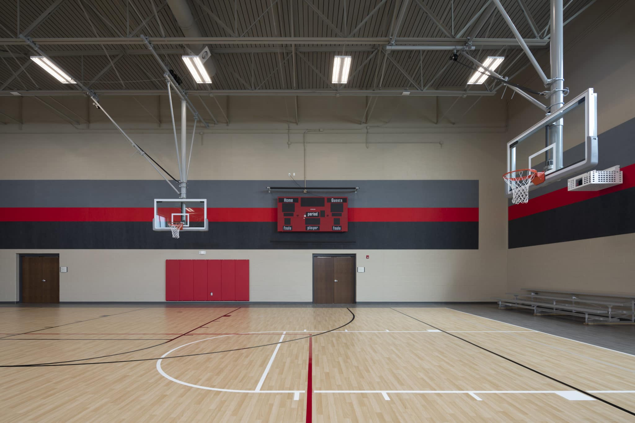 A gymnasium with two basketball hoops and a scoreboard