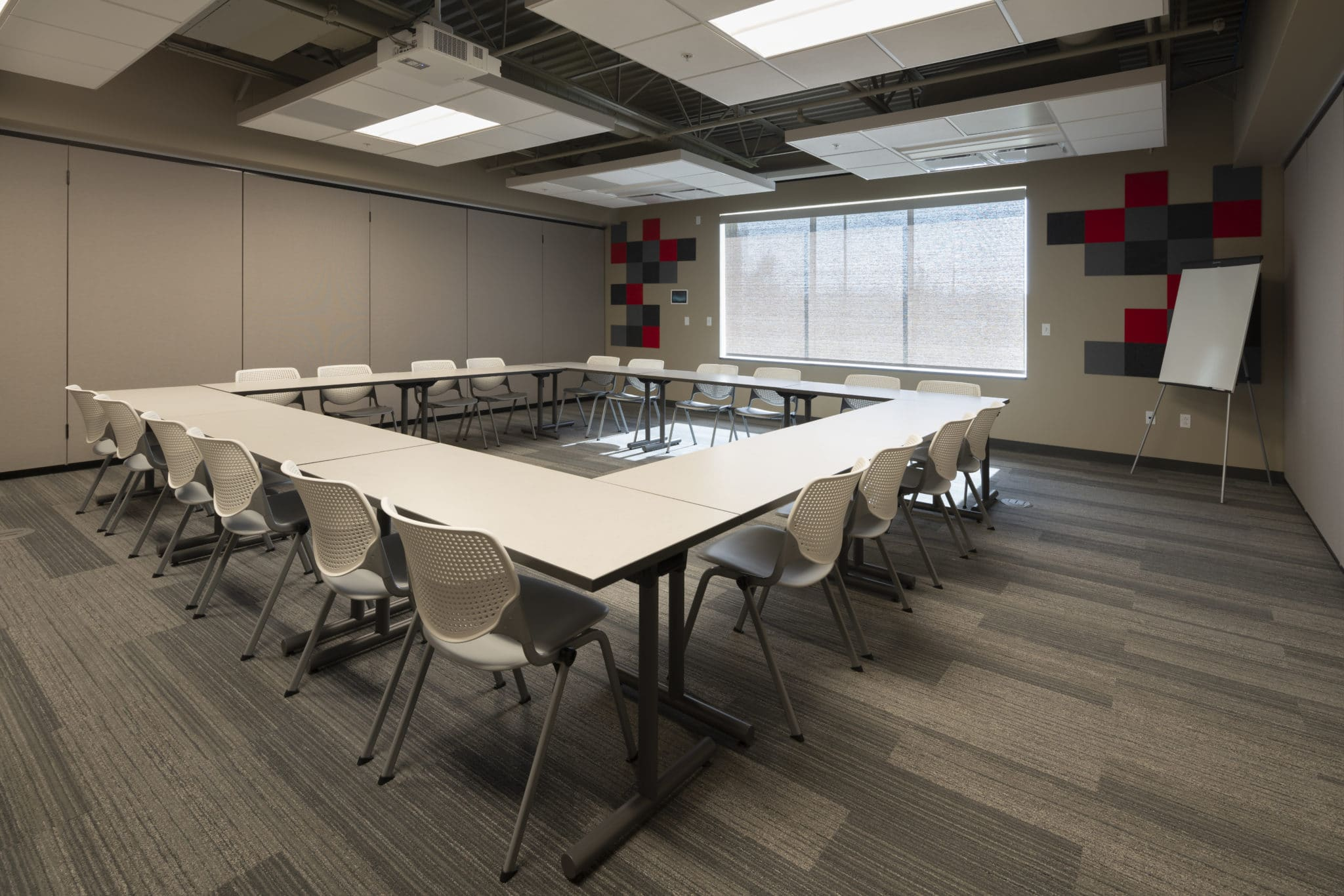 A group of tables pushed together in the form of a square with chairs around them in a conference room at the Training for Life Campus