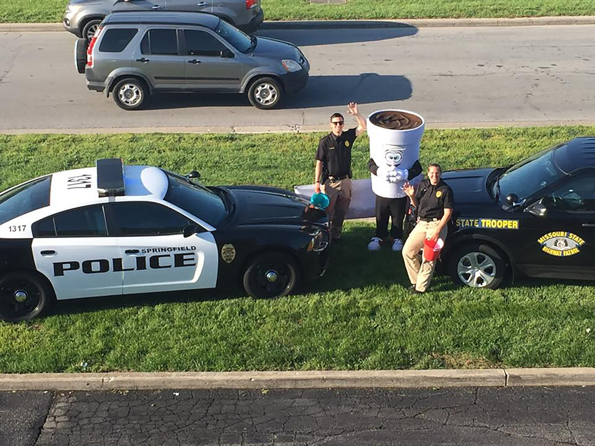 An aerial photo shows two law enforcement officers in front of their cop cars with a person wearing a coffee costume