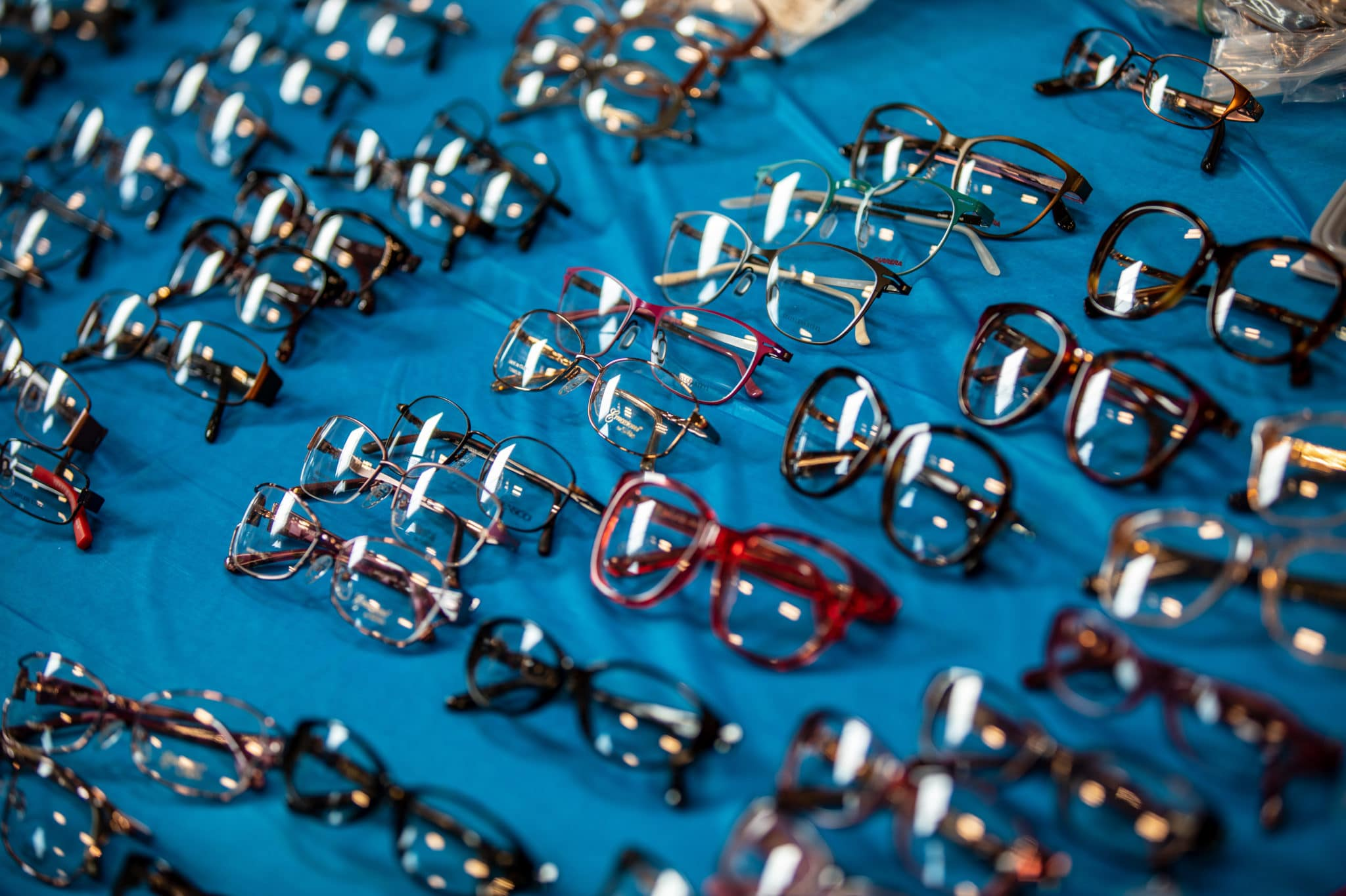 A collection of eyeglasses sit on a table available for SOMO athletes at no cost
