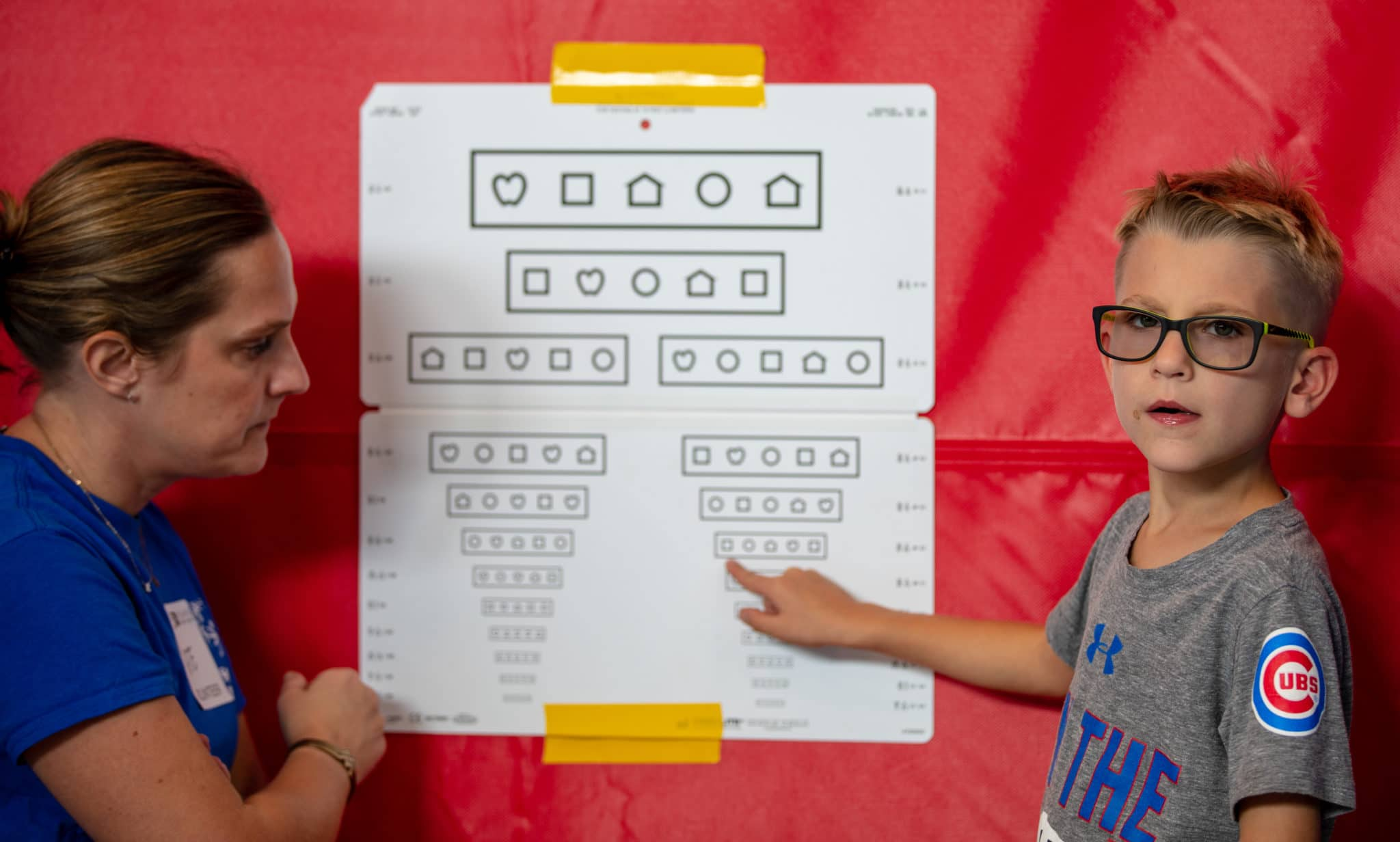 An athlete looks at the camera and points at an eye chart to let the volunteer know how far down the chart they can read