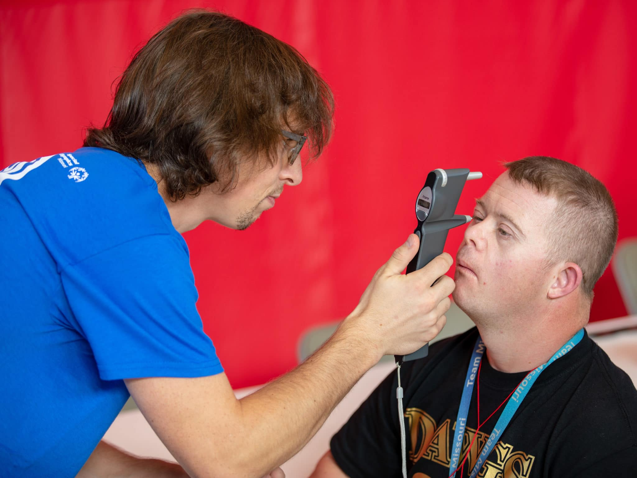 An athlete struggles to keep their eyes open as a volunteer uses an instrument to test their sight