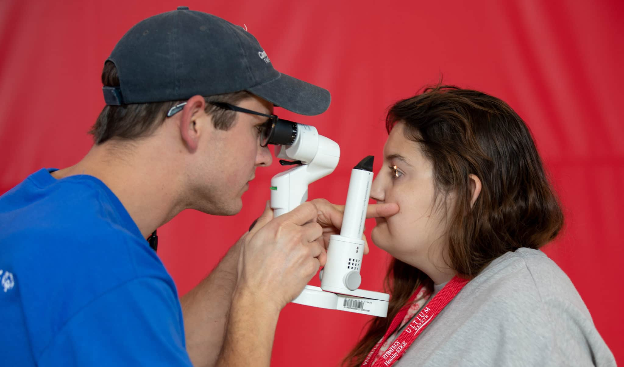 A volunteer uses eye exam equipment to look into the eyes of an athlete