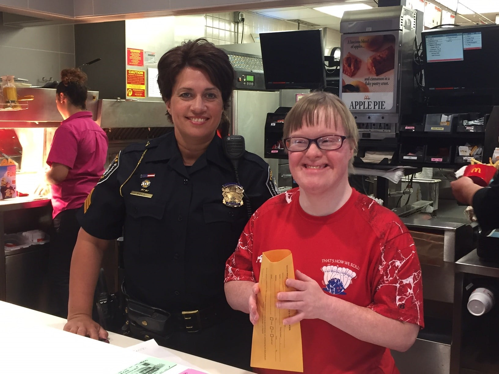 A law enforcement officer poses with an athlete holding a donation envelope and smiling at the camera