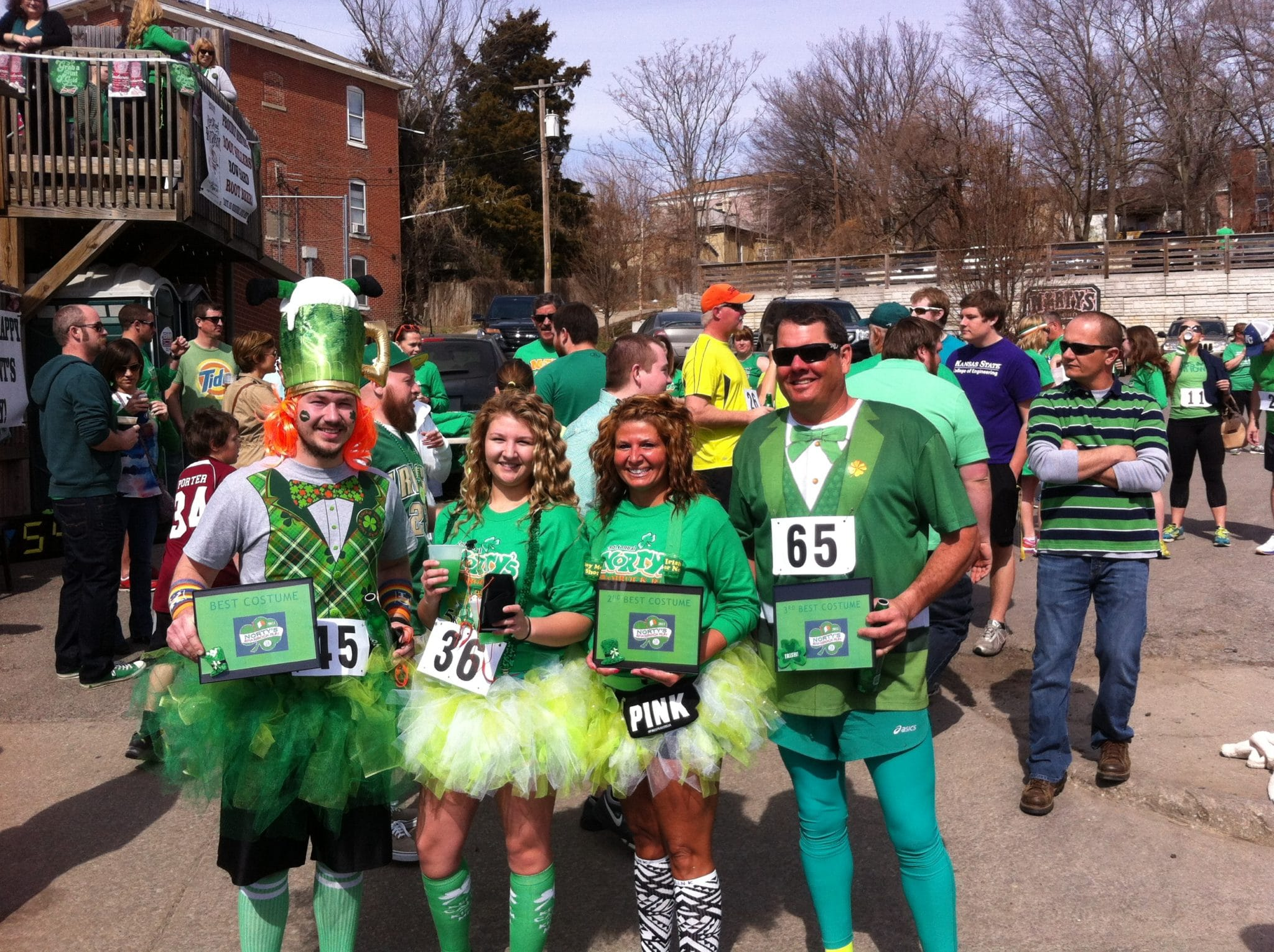 A group of people in green St. Patrick's gear pose for a photo
