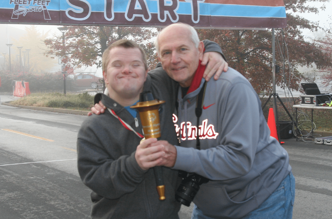 An athlete poses for a photo with a volunteer while holding a torch