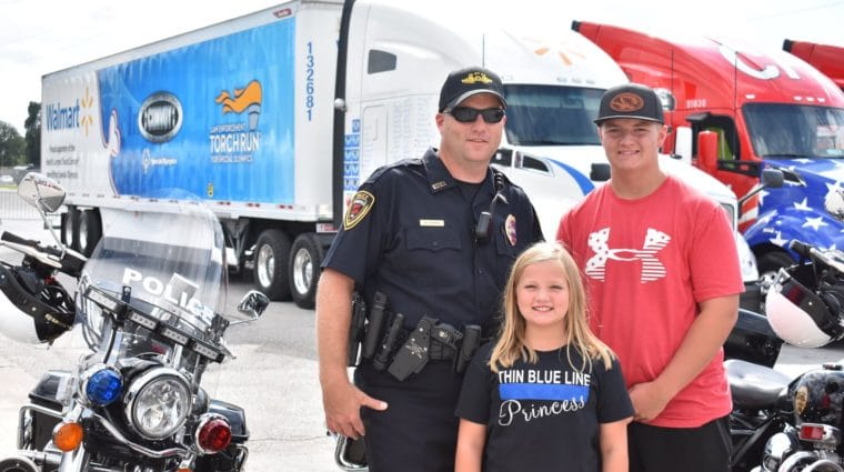 Sargent Mark Priebe poses for a photo with his two children in front of motorcycles and semi-trucks
