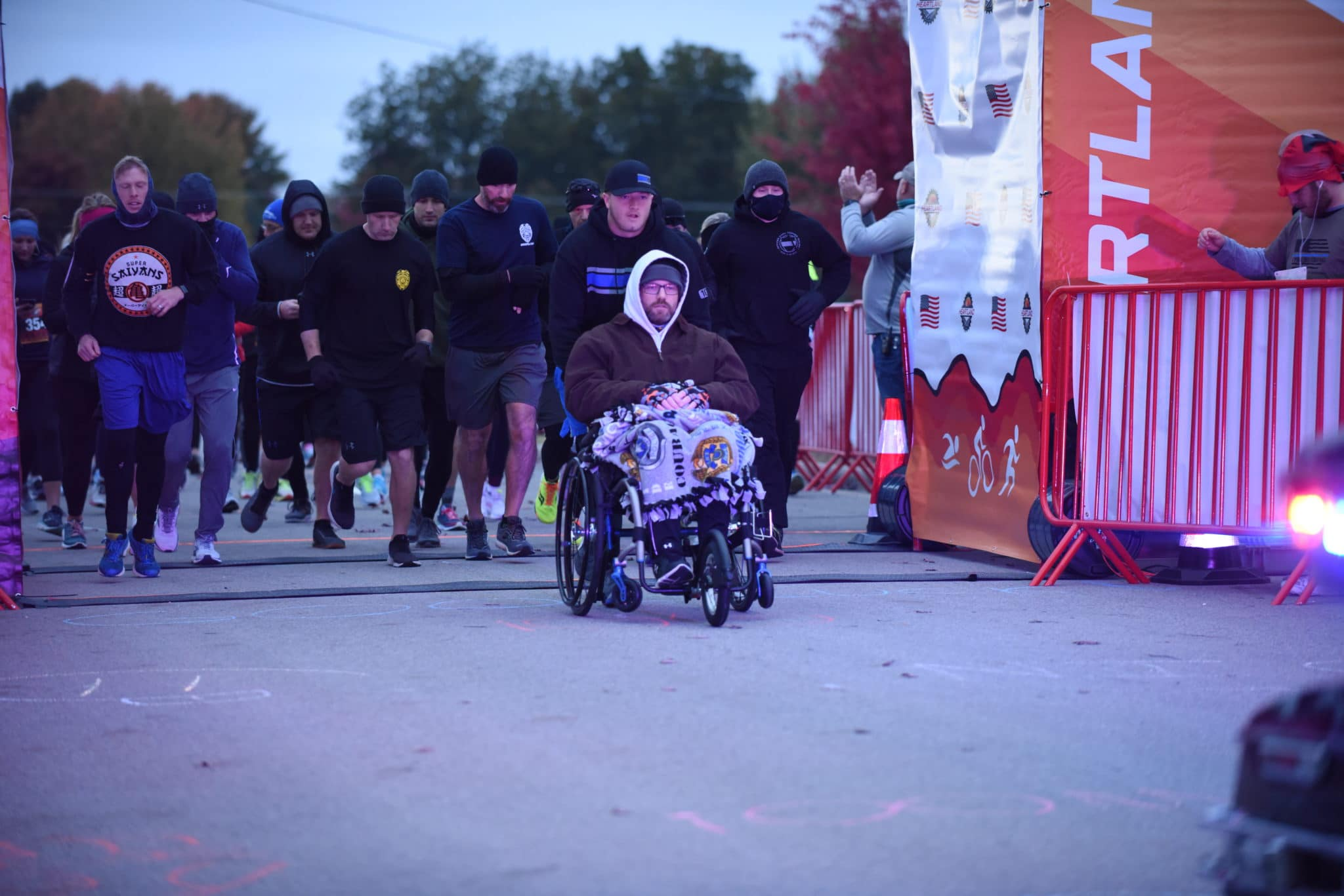 Sargent Mark Priebe is pushed in his wheelchair across the start line of a race by his son Connor Priebe while a crowd of runners follow behind