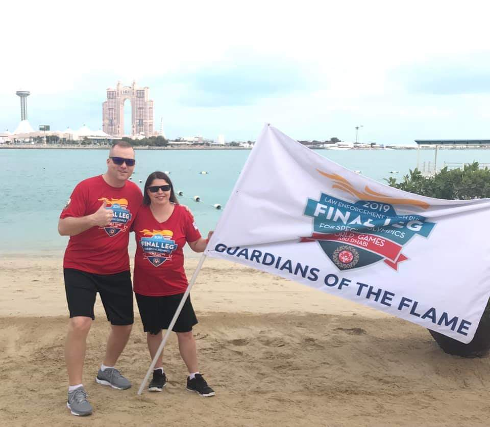 Mark Priebe and an athlete pose for a photo holding a LETR flag on a beach in Abu Dhabi