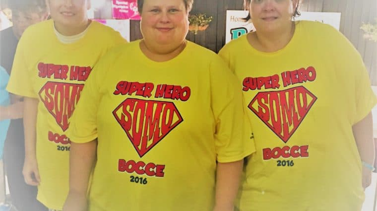 """Three athletes wearing """"Super Hero Bocce"""" shirts pose for a group photo"""