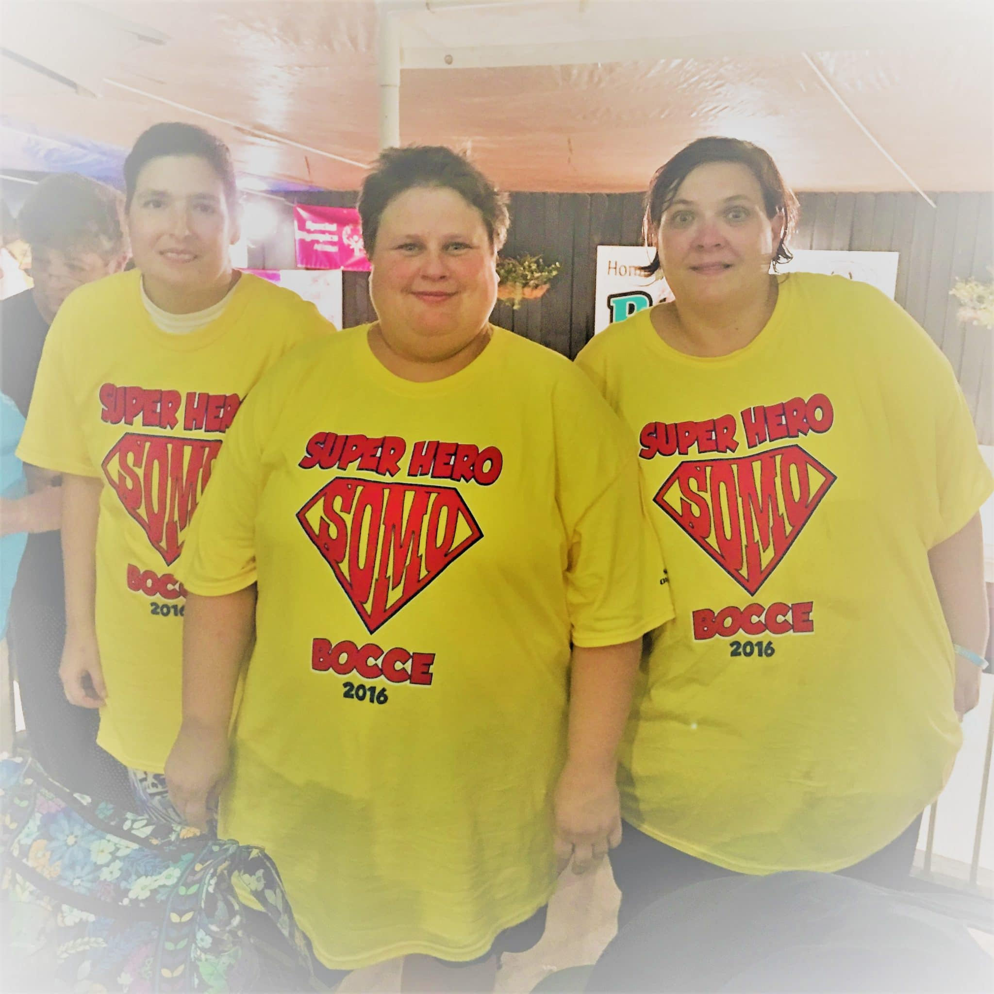 "Three athletes wearing ""Super Hero Bocce"" shirts pose for a group photo"