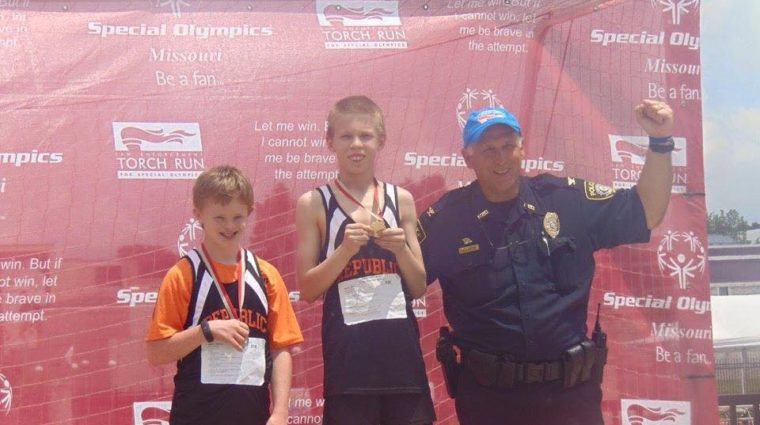 Two young athletes stand on a medal stand showing off their medals with a law enforcement officer raising their fist in the area and smiling