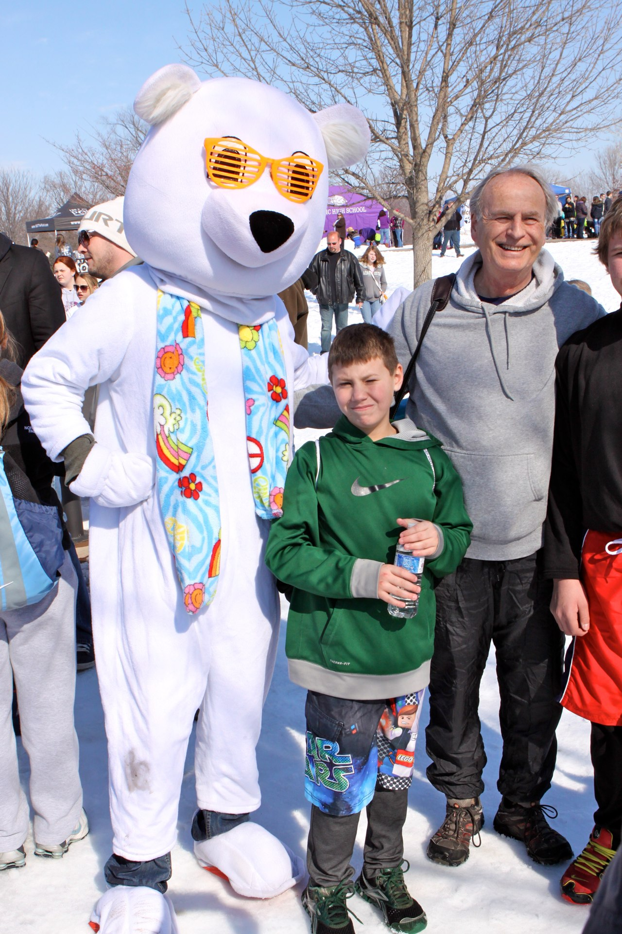 A mascot polar bear poses for a photo with a family at a Polar Plunge