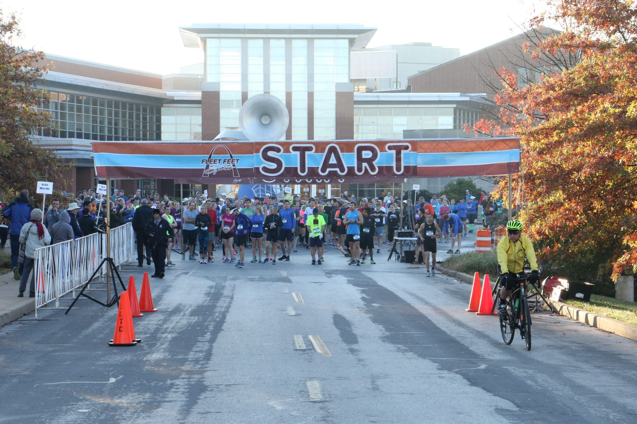 """A group of runners gather underneath a giant banner with """"START"""" on it"""