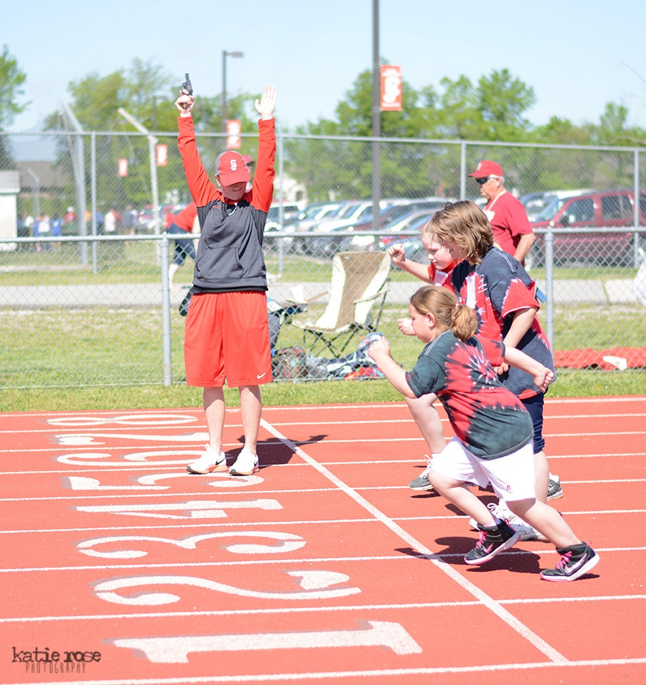 A group of athletes break off the starting line in track while a volunteer points a starter's pistol in the air