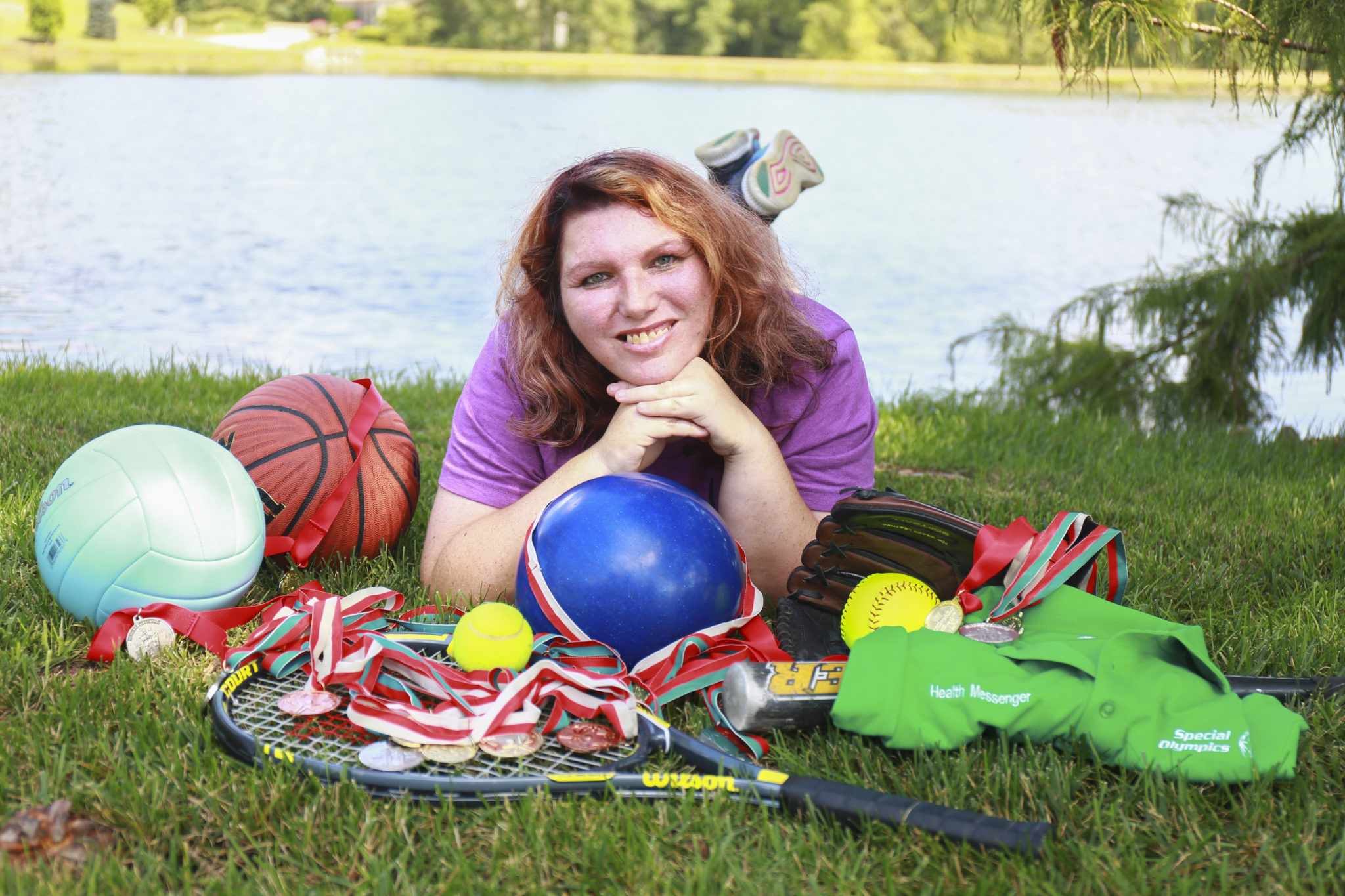 Athlete poses while laying on the ground and smiling at the camera surrounded by sports equipment