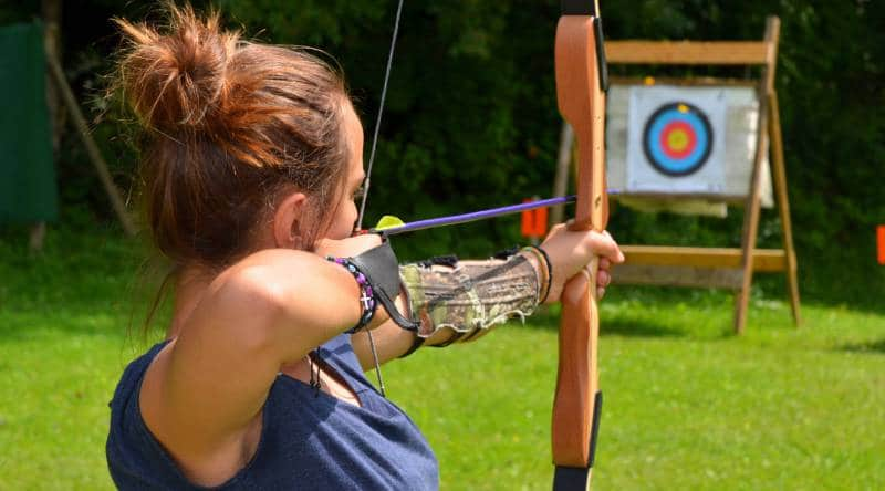 Person holding a bow and arrow and aiming at a target in front of them