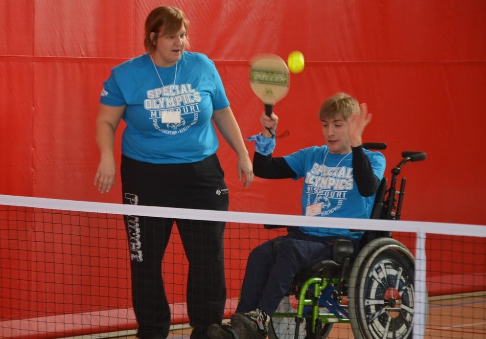A volunteer stands next to an athlete using a wheelchair swinging a paddle while playing pickleball