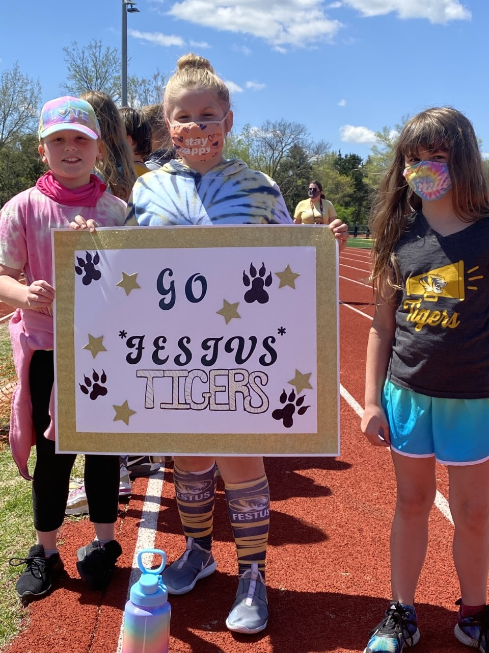 """Three young athletes pose for a photo while holding a sign that says """"Go Festus Tigers"""""""