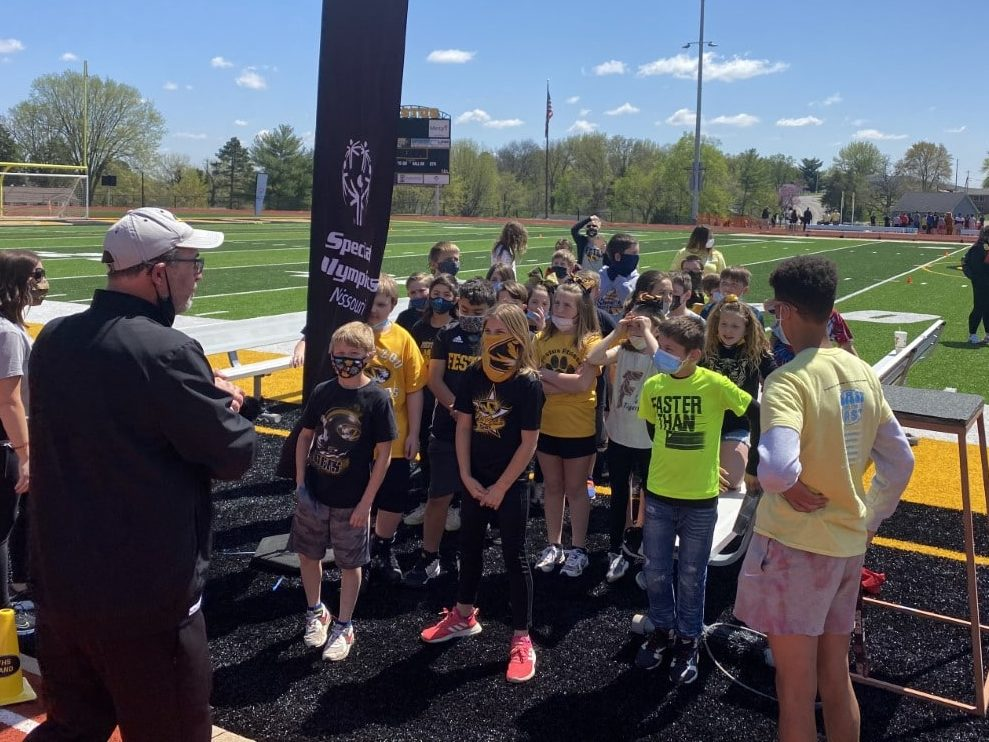 A group of young athletes stand in a group listening to a volunteer
