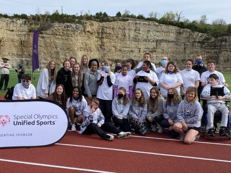 A group of athletes and volunteers pose for a photo on a track in front of a banner