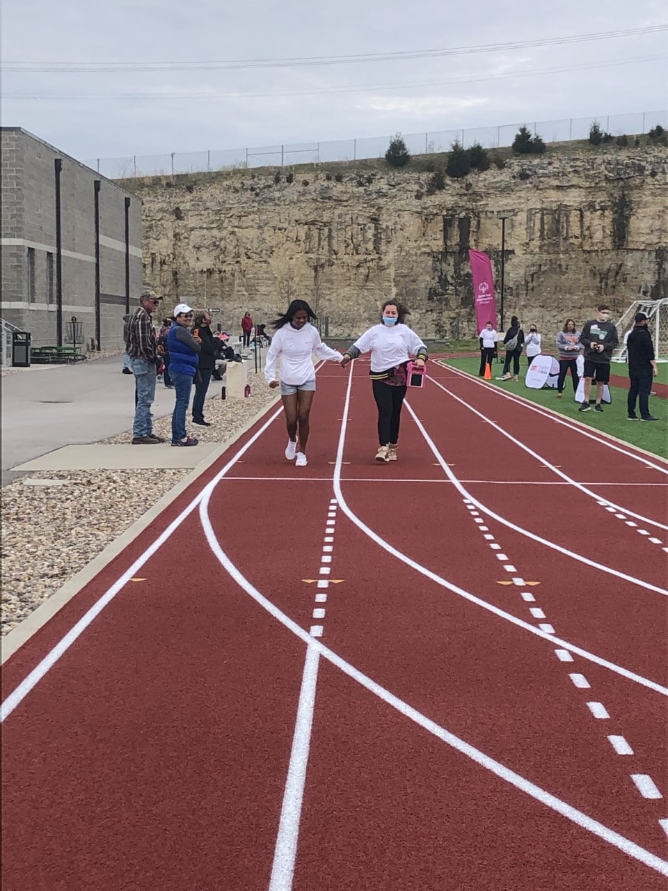 An athlete runs down a track while holding the hand of a volunteer