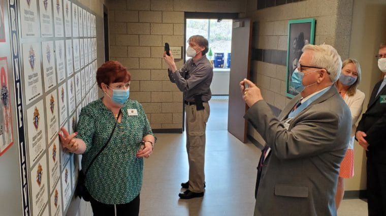 Knights of Columbus members Chris and Jerry Herbert, and Kurt Sommerhauser, take photos in front of the Knights of Columbus wall at the SOMO Training for Life Campus on April 25.
