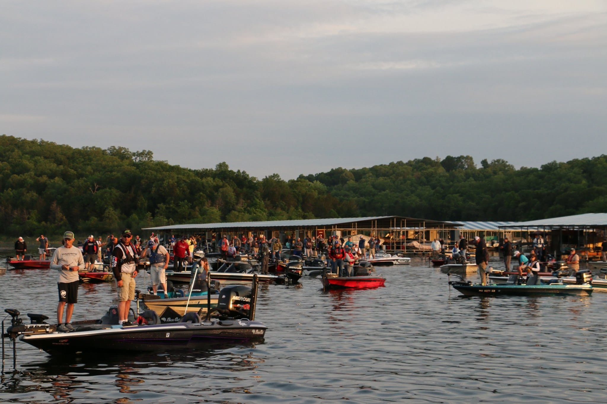 People stand on a large group of boats while fishing on the water