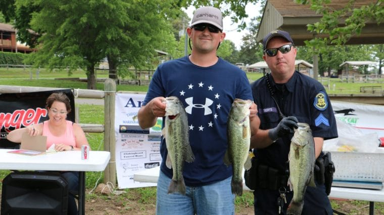 Two people pose for a photo while holding three fish