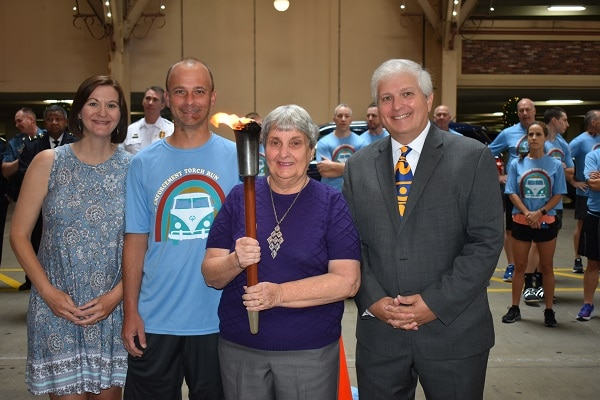 The Ottenad family with the torch for the Law Enforcement Torch Run for Special Olympics Missouri.