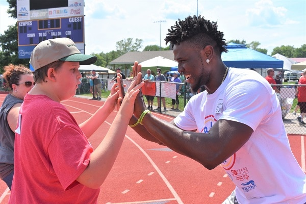 Volunteer Lucky Ogbodo of Jefferson City congratulates a runner at the end of a race during the 2021 State Summer Games.