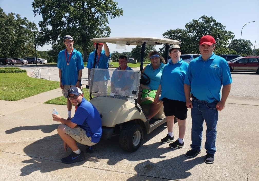 Athletes in bright blue shirts pose for a photo on the golf course in front of a golf cart