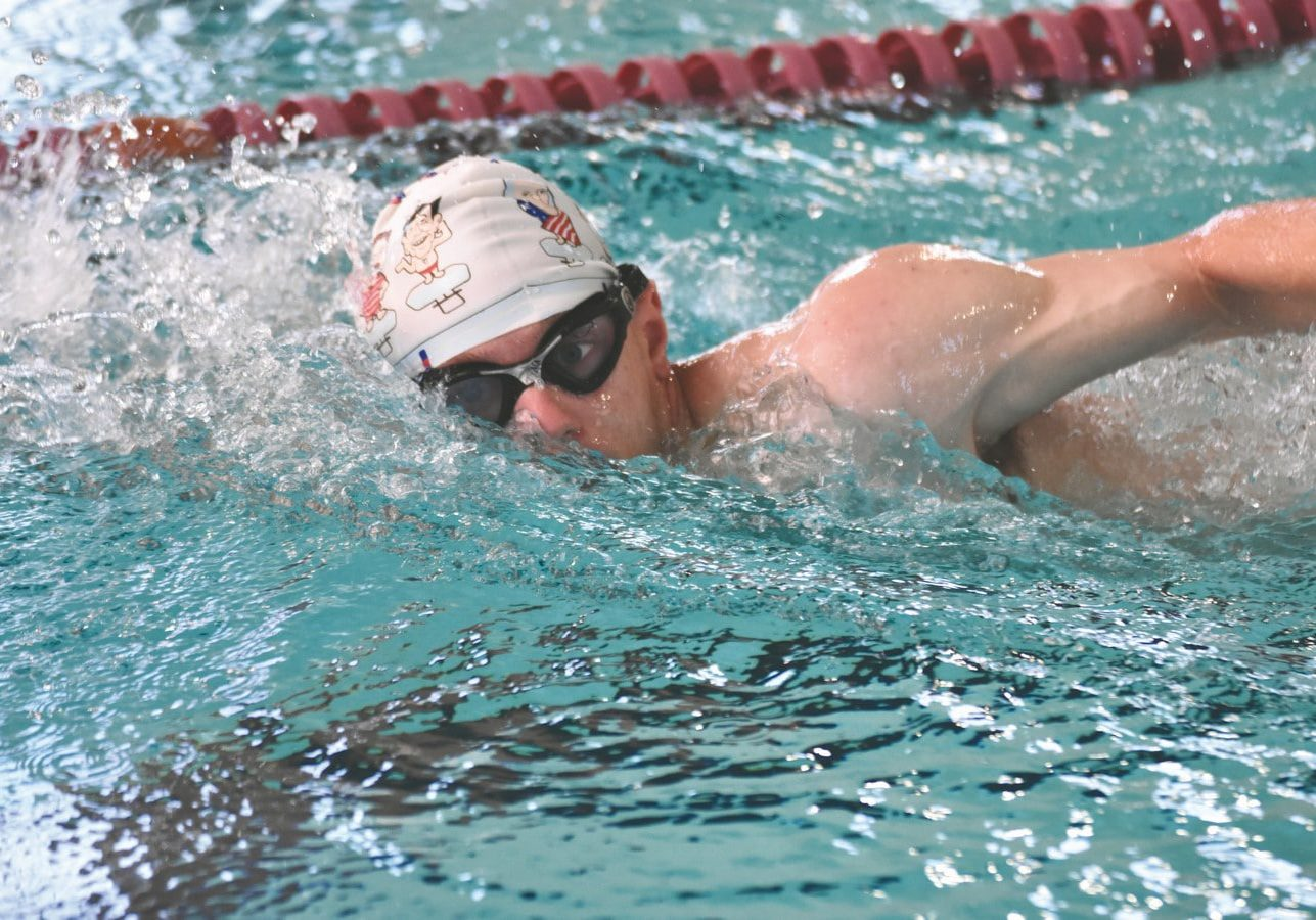 A swimmer's head barely breaks out of the water, half of their face still submerged in water