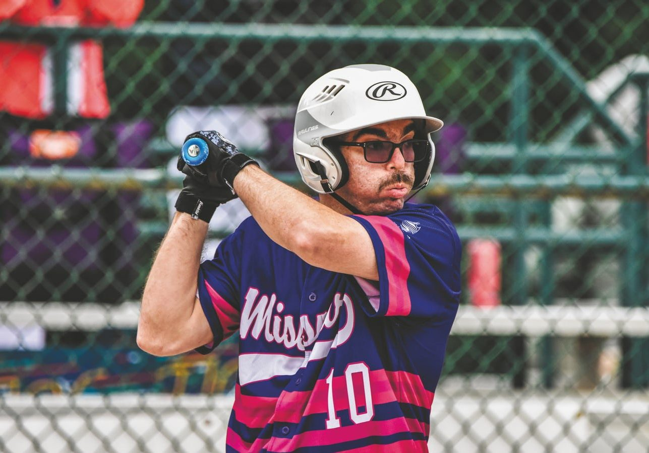 A softball athlete with a pink and purple Team Missouri uniform stands at-bat ready for a pitch while breathing slowly out of his mouth
