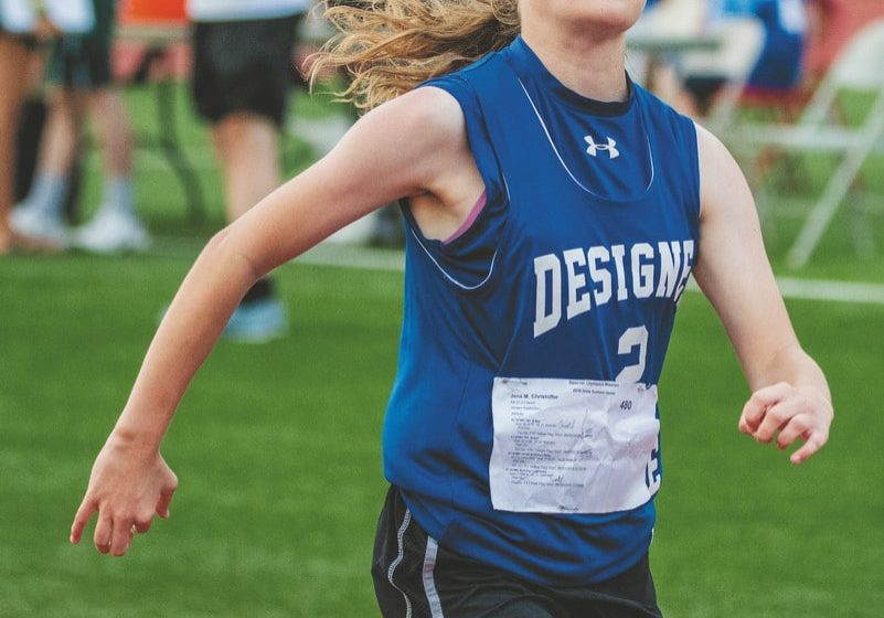 An athlete from Clever High School runs in a track and field race